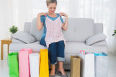 Blond woman with shopping bags trying out a top — Stock Photo