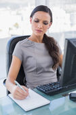 Frowning businesswoman taking notes — Stock Photo