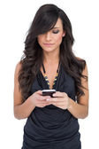 Concentrated brown haired model holding smartphone — Stock Photo