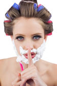 Secretive woman in hair curlers posing with shaving foam and raz — Stock Photo