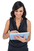 Smiling elegant brown haired model scrolling on tablet — Stock Photo