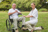 Hombre alegre en una silla de ruedas con su enfermera de rodillas al lado — Foto de Stock
