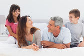 Smiling family talking together on bed — Stock Photo