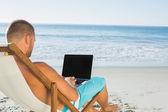 Bel homme, tapant sur son ordinateur portable tout en étant assis sur son chai de pont — Photo