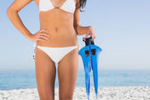 Perfect female body in white bikini holding fins — Stock Photo