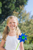 Cute blonde girl holding pinwheel smiling at camera — Stock Photo