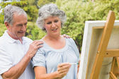 Happy retired woman painting on canvas and talking with husband — Stock Photo
