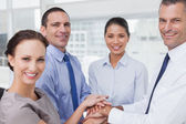 Cheerful work team joining hands together — Stock Photo