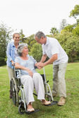 Mature woman in wheelchair with husband and daughter — Stock Photo
