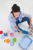 Happy woman sitting on floor with paint — Stock Photo