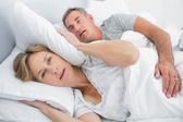 Irritated wife blocking her ears from noise of husband snoring — Stock Photo