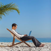 Young businessman on his beach chair using his laptop — Stock Photo