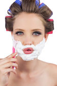Sexy young model in hair curlers posing with razor — Stock Photo