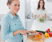 Blonde woman cutting carrots with her friend tossing salad — Stock Photo