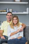 Lachende paar zitten op hun bank — Stockfoto