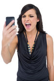 Angry elegant brown haired model screaming to her phone — Stock Photo