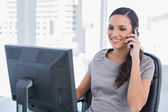 Smiling dark haired businesswoman having a phone conversation — Stock Photo