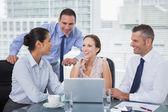 Vrolijke collega's rond laptop samen te werken — Stockfoto
