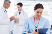Nurse writing on a clipboard while doctors are talking together — Stock Photo