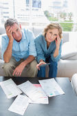 Anxious couple sitting on their couch paying their bills — Foto Stock