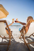 Couple clinking their glasses while relaxing on their deck chair — Stock Photo