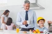 Lustige kleine Junge Väter Bauarbeiterhelm während des Frühstücks zu tragen — Stockfoto