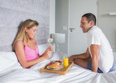 Happy woman being brought breakfast in bed by husband — Stock Photo