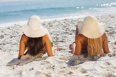 Attractive blonde and brunette in bikinis lying on the sand — Stock Photo