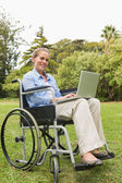 Smiling young woman in a wheelchair with a laptop — Stock Photo