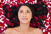 Pensive sensual dark haired model lying in rose petals — Stock Photo