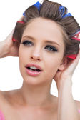 Model with hair curlers touching her hair — Stock Photo