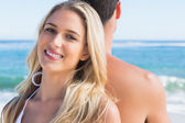 Blonde smiling and leaning against her boyfriend — Stock Photo