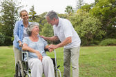 Happy woman in wheelchair with husband and daughter — Stock Photo