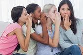 Friends whispering secret to shocked brunette — Stock Photo