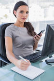 Sexy businesswoman using calculator and writing — Stock Photo
