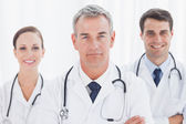 Cheerful doctors posing together crossing arms — Stock Photo
