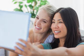 Two pretty friends taking photo with tablet pc — Stock Photo