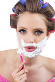Young model in hair curlers posing with razor — Stock Photo