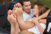 Cute couple cuddling in the backseat with focus on foot — Stock Photo