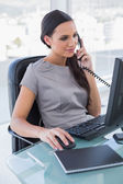 Concentrated businesswoman answering phone and working on comput — Stock Photo