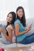 Friends sitting back to back with their tablets smiling at camer — Stock Photo