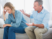 Middle aged couple sitting on the couch having a dispute — Stock Photo