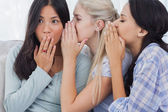 Two friends whispering secrets to shocked brunette — Stock Photo