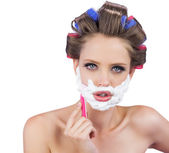 Delightful model in hair curlers posing with razor — Stock Photo