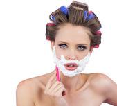 Delightful model in hair curlers posing with razor — Stock Photo