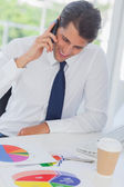 Smiling businessman on the phone analyzing graphs — Stock Photo