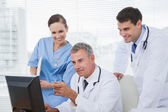 Doctors and surgeon working together on computer — Stock Photo