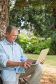 Oude man kijken naar zijn laptop — Stockfoto