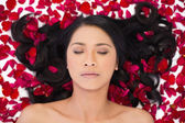 Relaxed attractive dark haired model lying in rose petals — Stock Photo