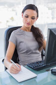 Concentrated businesswoman taking notes — Stock Photo